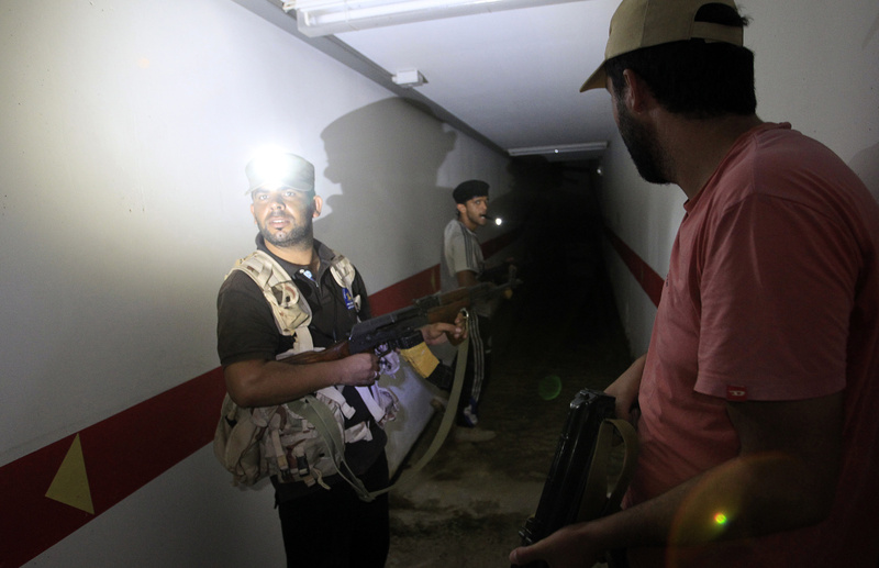 Rebel fighters inspect a tunnel in the bunker under Moammar Gadhafi's compound in Bab Al-Aziziya in Tripoli, LIbya, on Thursday. Existence of the tunnel system beneath the compound has long been rumored, and rebels discovered an extensive system that had many rooms, multiroom complexes and caches of food.
