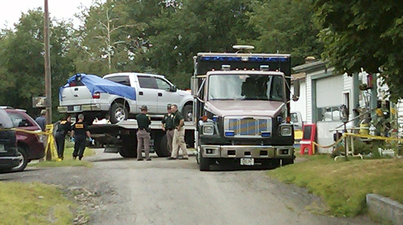 This cell phone photo shows law enforcement officials standing near a silver pickup truck being removed from where it was parked near the home of Celina Cass, in Stewartstown, N.H., today.