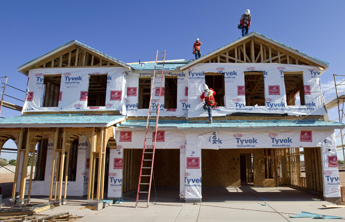 Builders frame a new home in Queen Creek, Ariz., on Monday. The number of people who bought new homes fell for the fourth straight month.