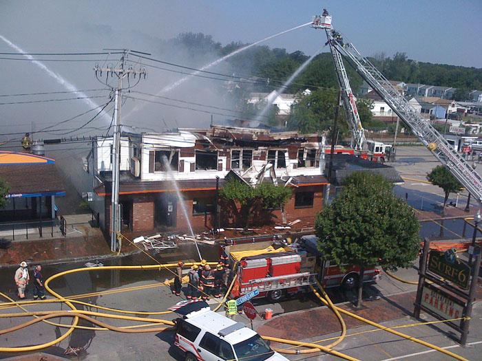 Firefighters on four ladder trucks pour water on the Galaxy night club on East Grand Avenue in Old Orchard Beach late this morning.