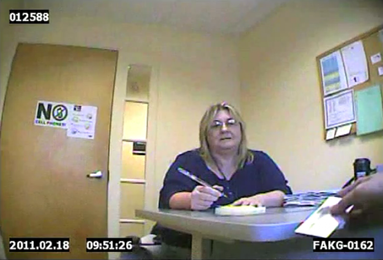"""Screen capture from video of a Department of Health and Human Services worker talking with """"Ted Ceanneidigh,"""" not shown, a man trying to receive Medicaid benefits while broadly hinting that he is a drug smuggler."""