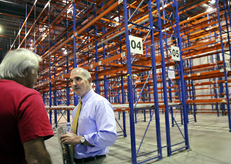 Nick Alberding, right, managing partner and an owner of Pine State Trading, gets a tour through the refrigerated storage at the former Associated Grocers warehouse from former AG employee Tom Doucette before an Aug. 8 auction for AG's buildings in Gardiner. Pine State Trading purchased the property from Camden National Corporation on Wednesday.