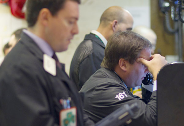 Traders work on the floor of the New York Stock Exchange today. All three major stock indexes are down 10 percent or more from their previous highs, a drop-off that is considered to be a market correction.