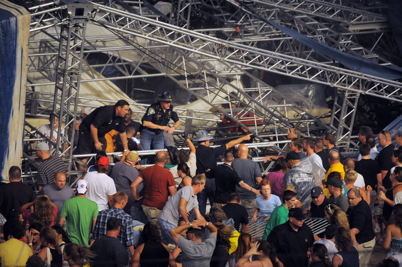 Fans waiting to see Sugarland attempt to hold up the stage after high winds blew the stage over at the Indiana State Fair Grandstands, Saturday in Indianapolis. Five people were killed.