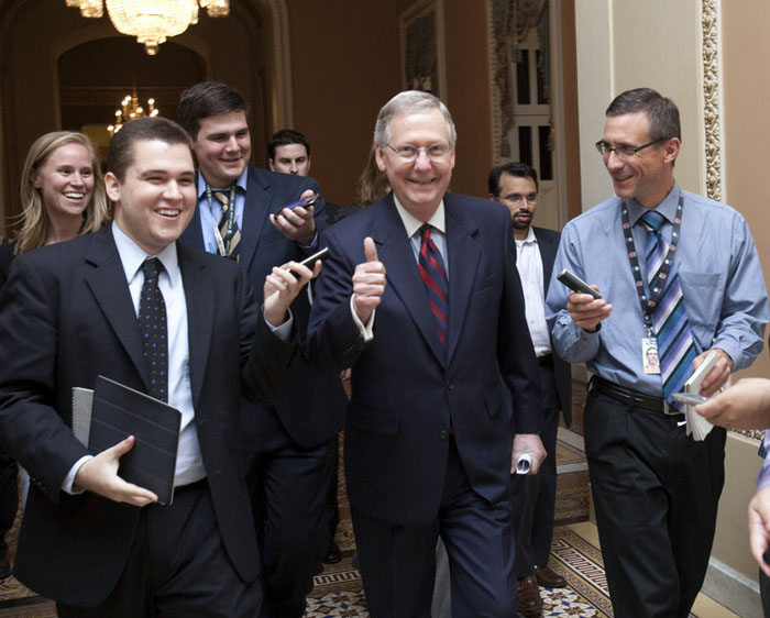 Senate Minority Leader Mitch McConnell, R-Ky., is all smiles as he walks to the Senate floor to announce that a deal has been reached on the debt ceiling on Capitol Hill on Sunday.