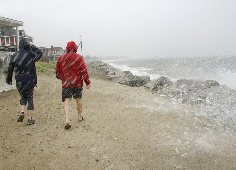 A couple walks along Surf Street in Saco as Tropical Storm Irene sends waves up over the rocks this morning.