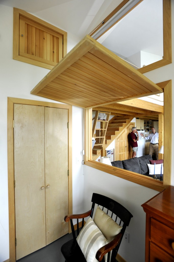 A wooden door drops down to close a pass-through between the bedroom and the living area.