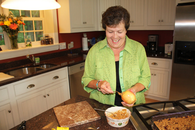 Vesta Rand stuffs a cored apple with a mixture of peanut butter, dried fruit, nuts and seeds in her Yarmouth kitchen for her prize-winning Mackworth Island Walking Salad.