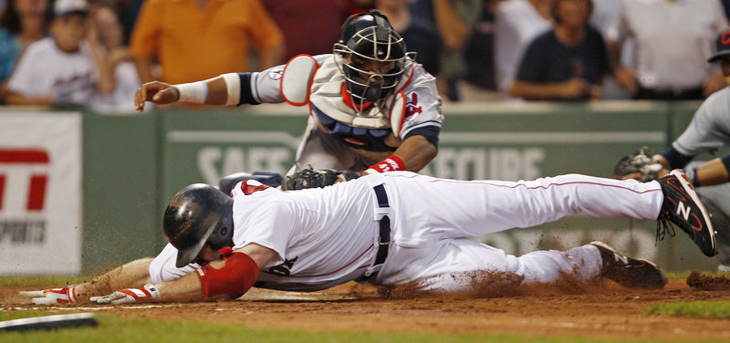 Indians catcher Carlos Santana tags out Boston's Kevin Youkilis at the plate in the third inning Monday night. Youkilis was out trying to stretch his triple.