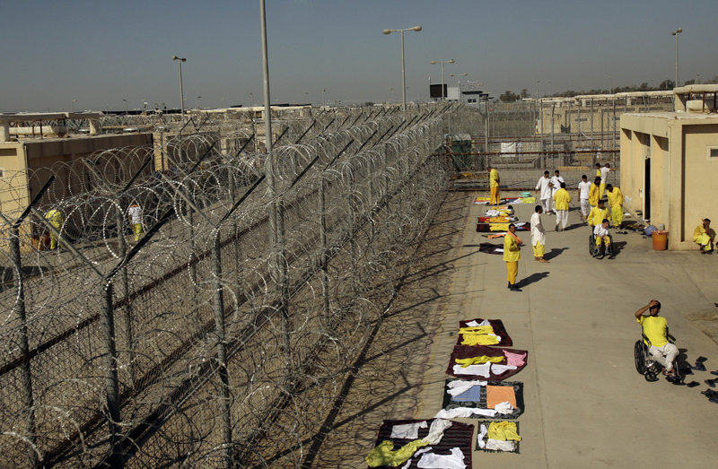 Detainees mingle outside their cell block at Camp Cropper, the U.S. detention facility in Baghdad, in 2008. A former contractor for the U.S. military says he was repeatedly abused while held at the camp for nine months.