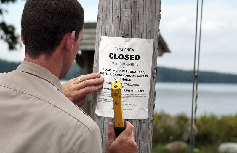 """Maine Marine Patrol Officer Rob Beal posts a """"closed to all digging"""" sign Thursday at Maquoit Bay in Brunswick. When clam flats are closed, it's usually because of poor water quality caused by contamination carried by faulty septic systems and surface runoff."""