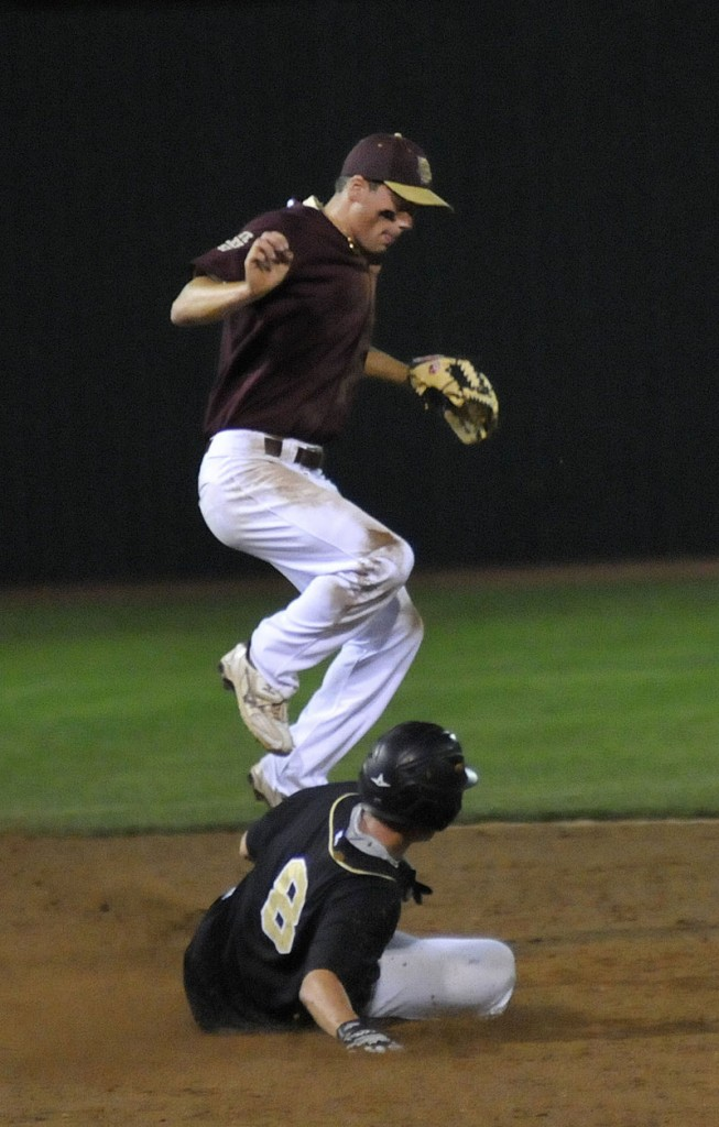 Sam Canales of Fayette-Staples, the host team, leaps as Nick Ferguson of Colchester, Vt., steals second base.