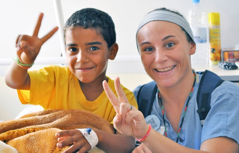 Sophie Belanger, a nurse from Maine Medical Center, poses with a young patient during an instructional visit at the Benghazi Medical Center in Libya.