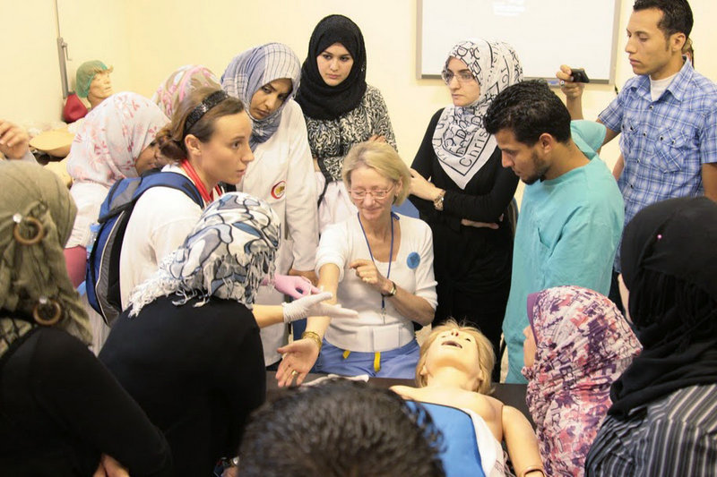 Elizabeth McLellan, center, and Sophie Belanger, left, show Libyan medical students in Benghazi how to properly insert an IV into a patient's arm. McLellan is the founder of Scarborough-based Partners for World Health.