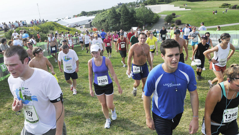 The race is over – a race held in muggy conditions – and the Beach to Beacon runners at Fort Williams in Cape Elizabeth head up a hill to the water stations for a well-deserved drink.