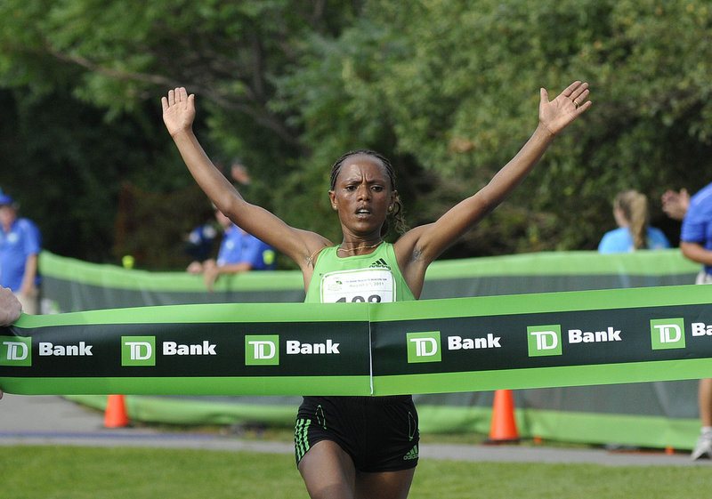 Aheza Kiros raises her arms as she crosses the finish line and captures the elite women's championship at the Beach to Beacon 10K road race on Saturday in Cape Elizabeth. Kiros survived on a hot day to finish in 32:08.7.