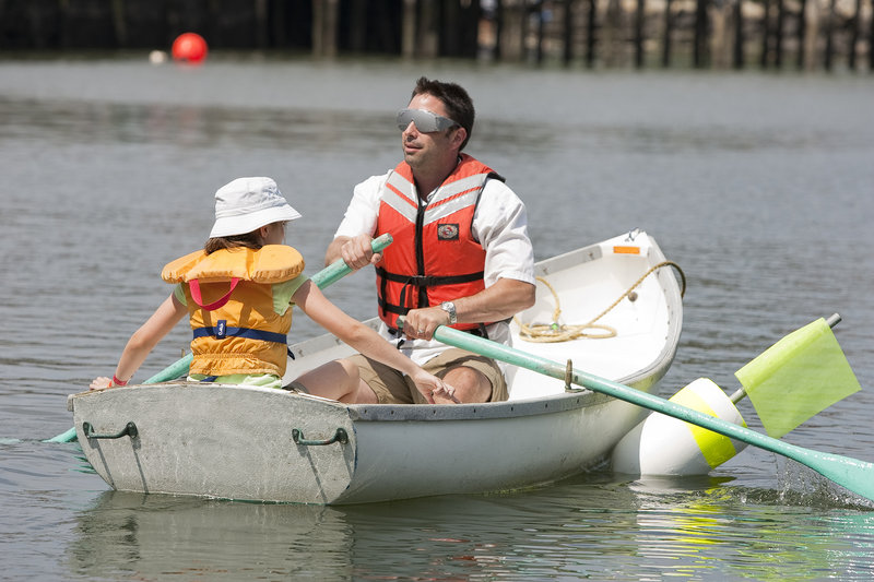 Daughter Bella guides blindfolded Vinny Lesinski of Rowley, Mass., during the Blindfold Rowboat Race.