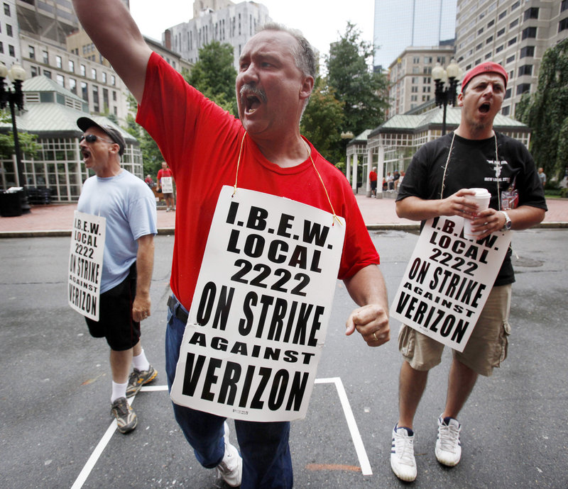 Verizon worker PJ Foley, center, of Quincy, Mass., leads a chant while picketing outside a Verizon headquarters in Boston on Sunday. About 45,000 Verizon workers, from Massachusetts to Washington, D.C., went on strike Sunday.
