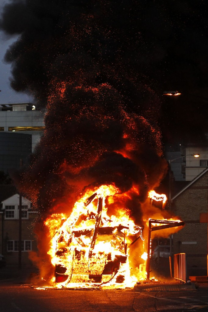 A bus burns as rioters gather in Croydon, south London, on Monday. Violence and looting spread across some of London's most impoverished neighborhoods on Monday.