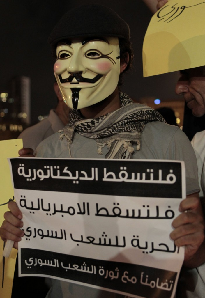 "A masked protester holds a placard Monday that reads in part, ""Down with dictatorship, freedom for the Syrian people,"" during a sit-in by Lebanese intellectuals and journalists."