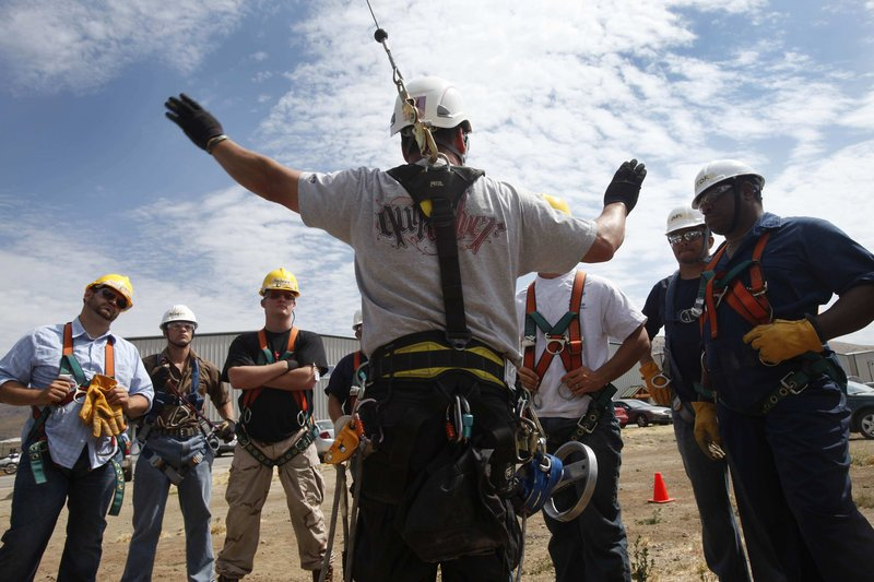 Wind and oil industry safety instructor Carl Mosby talks to his students, most of whom are military veterans, about their next exercise: rappelling from a 30-foot mobile training tower in Tehachapi, Calif.