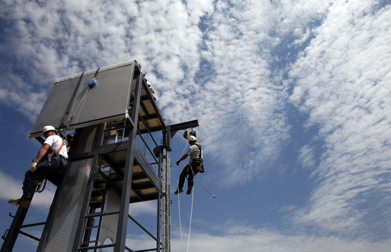 Students of Airstreams Renewables, a Tehachapi, Calif., company that offers safety and rescue courses for wind turbine, oil and gas employees, learn rappelling techniques from instructor Carl Mosby, dangling at right. A rise in green energy technologies has brought new workplace dangers and a need for new safety standards.