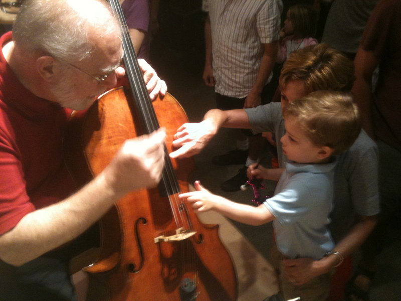 Cellist Marc Johnson introduces a toddler to string instruments.