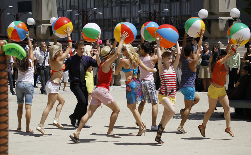 Actors dressed in beach attire participate in a flash mob as part of a commercial for McDonald's in Chicago. Such events are now being organized for malicious purposes.