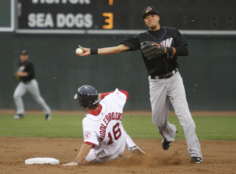Juan Diaz of Akron avoids a slide by Will Middlebrooks of the Sea Dogs and throws to first to complete a double play in the second inning.