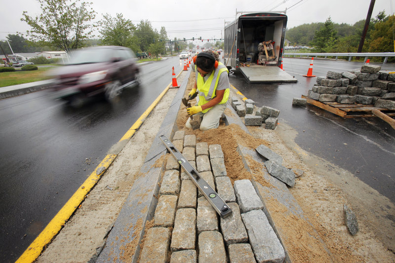 Frank Navarro places landscaping cobbles into the median near the intersection of Route 1 and Haigis Parkway Wednesday in Scarborough, one of two projects aimed at easing bottlenecks on Route 1. So far, local reaction to the work has been mixed.