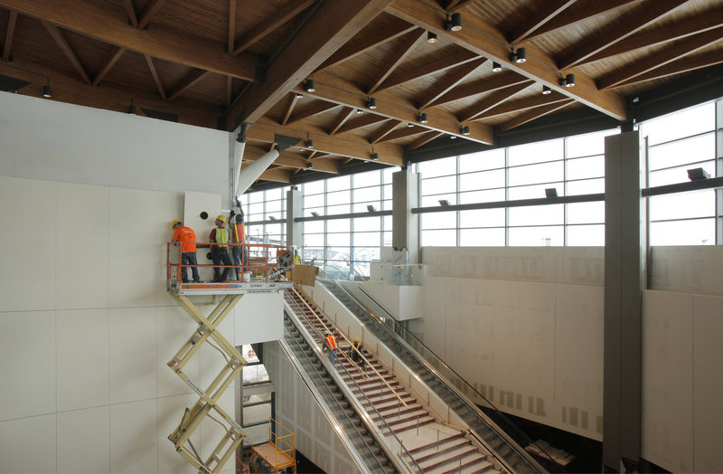 """Workers install wall panels Wednesday inside the expanded terminal at the Portland International Jetport. The new facility goes """"live"""" at 4 a.m. on Oct. 2."""