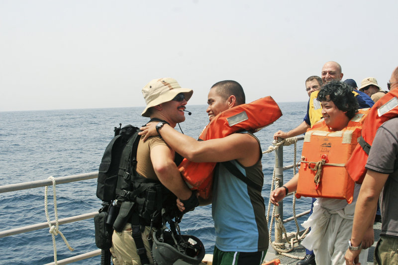 Lucas Alderette, left, of the USS Philippine Sea says goodbye to a sailor rescued from the tanker Brillante Virtuoso last month in the Gulf of Aden.
