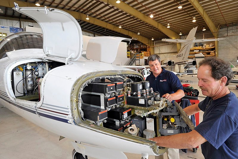 Travis Caruso, left, director of maintenance for Maine Aviation Corp., talks with Wayne Clark, an aircraft technician, during an Inspection of a Citation 550 in the company's maintenance hangar at Portland International Jetport.