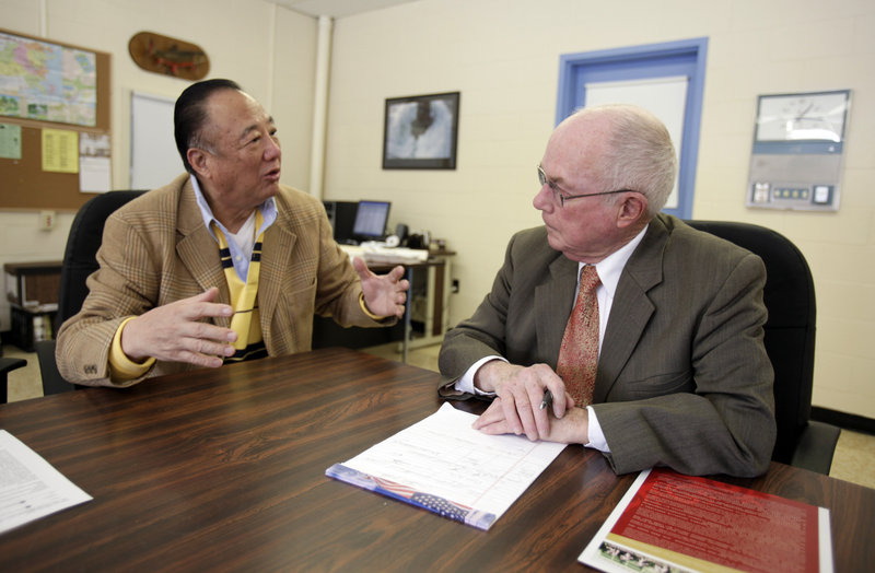 Millinocket school Superintendent Ken Smith, right, talks to Tony Yu of the U.S. China Cultural Exchange Committee last March. Local officials say they'll stick with a plan to recruit Chinese pupils and try to expand enrollment in the years ahead.