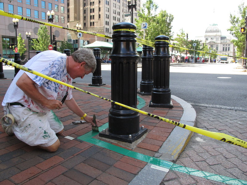 Robert Burke paints a corner of the new Independence Trail in Providence, R.I. The walking route through the city's historic sites is set to be completed today.
