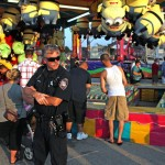 Extra law enforcement officers patrol the Wisconsin State Fair last week because of recent mob attacks at a fair in West Allis, Wis. On the opening night of that fair, 31 people were arrested and at least 11 people were hurt.