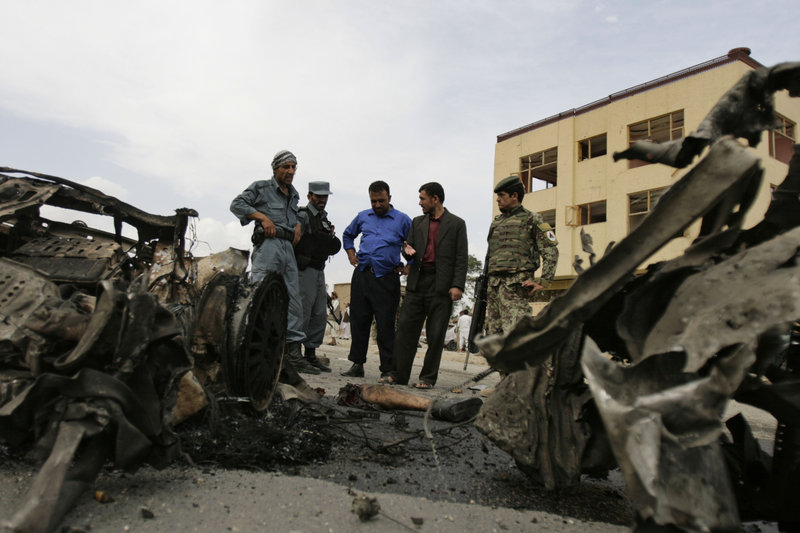Afghan police officers and soldiers inspect the site of a car bombing Sunday in the Parwan provincial capital of Charikar, some 30 miles north of Kabul, Afghanistan. Sixteen civilian government employees and six police officers were killed.