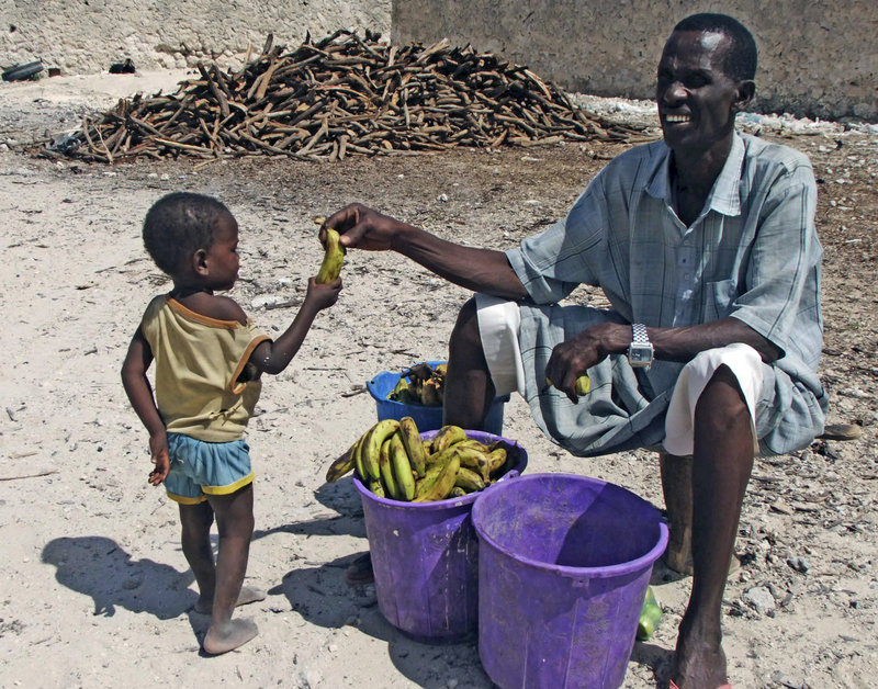 A Somali child receives a banana from a vendor outside a refugee camp in Mogadishu. Refugees say they are often made to return food after they've been photographed with it.