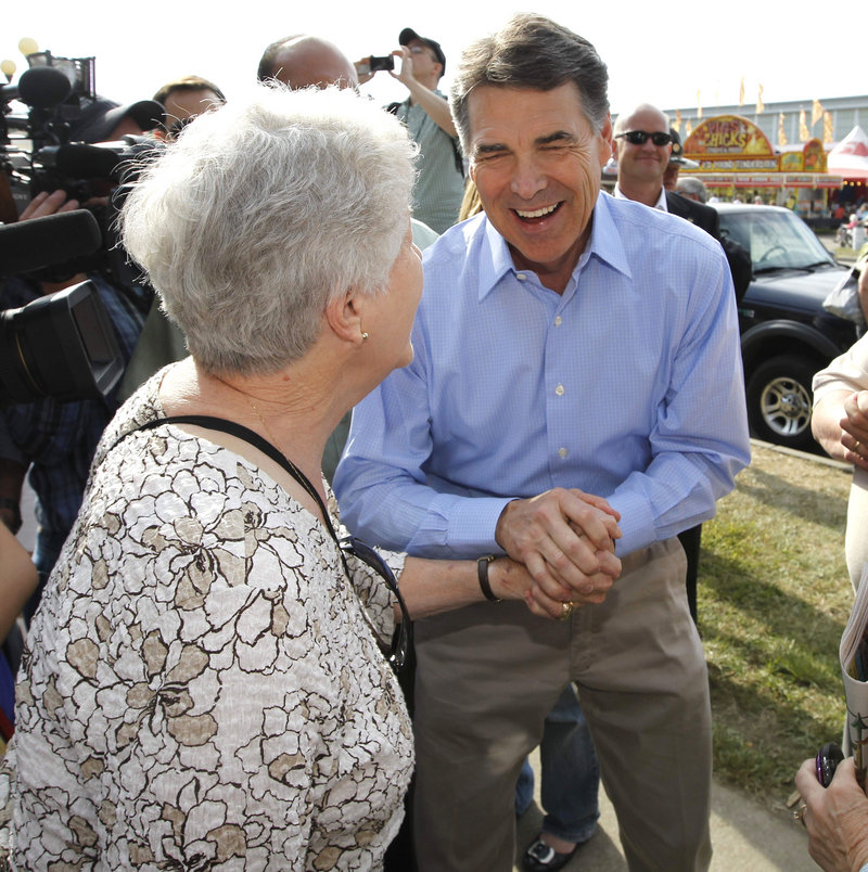Rick Perry greets visitors at the Iowa State Fair Monday. He entered the race Saturday and immediately gained top-three status in the GOP field.