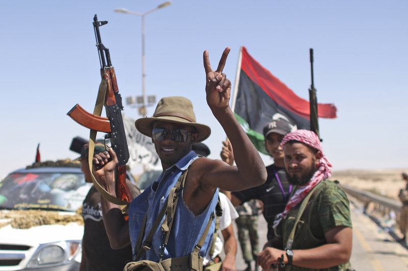 A rebel fighter celebrates Monday at the gates of the town of Brega, Libya. They said most of the town has been liberated from Moammar Gadhafi's troops. Rebls said they were trying to take refineries in Zawiya, 30 miles from the capital, Tripoli.