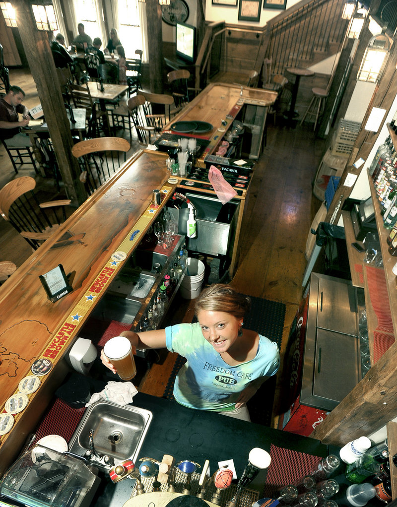 Bartender Annie Foster holds a draft beer at Freedom Cafe and Pub in Naples, located in a 200-year-old converted post-and-beam structure overlooking the edge of Long Lake.