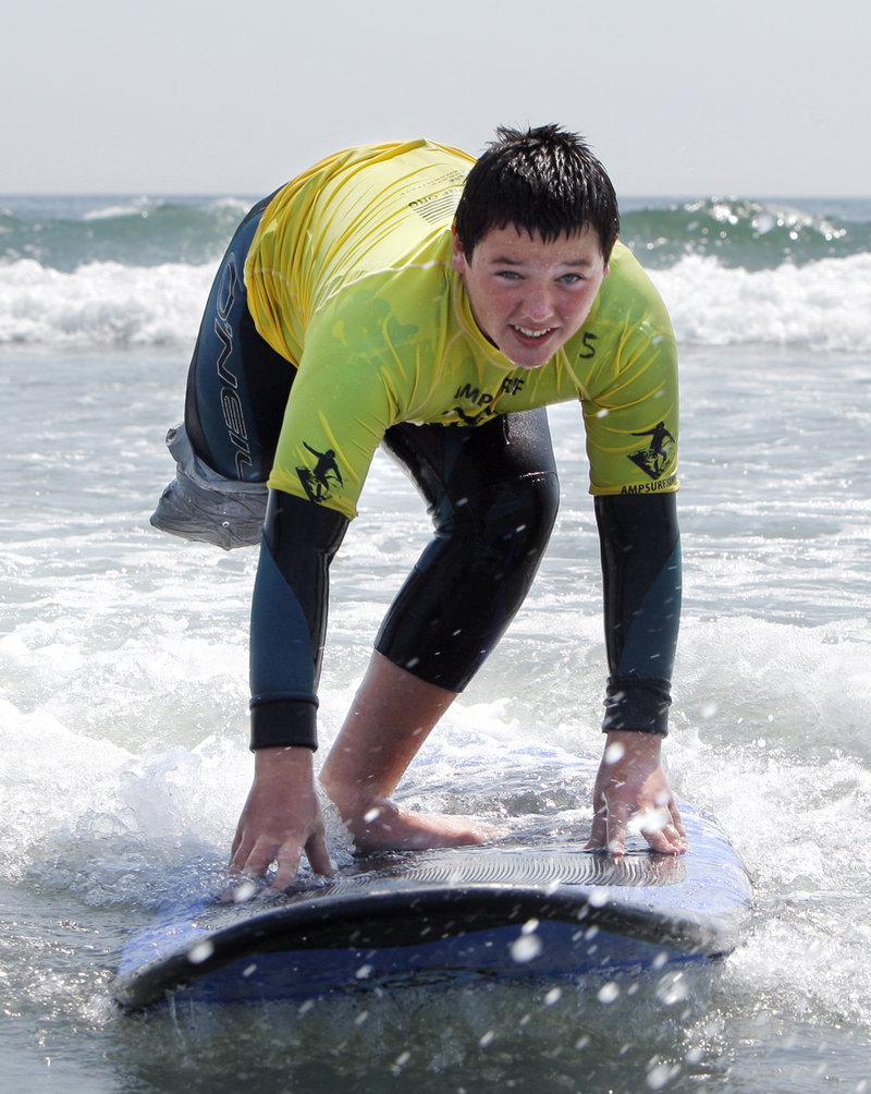 Jack Wallace, 13, surfs at Long Sands Beach in York on Thursday. Wallace traveled from New Jersey to participate in a surf clinic held by AmpSurf, an organization that teaches people with disabilities how to surf. Another clinic will he held at the same location today.