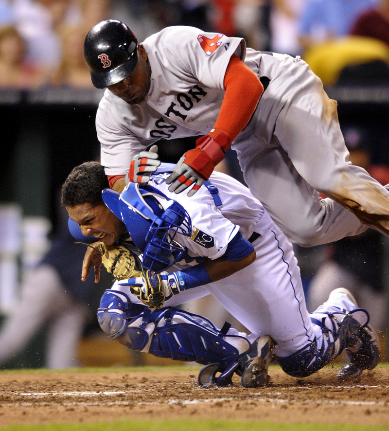 Kansas City catcher Salvador Perez holds on for the out Thursday night as Carl Crawford of Boston tries to score from third on a fly ball by Mike Aviles.