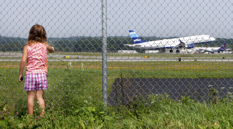 Hannah Jacob, 4, watches a JetBlue plane take off at the Portland International Jetport on Friday. She usually visits the plane-spotting area along Aviation Boulevard in South Portland twice a week with Cindy Griffin, her caregiver.