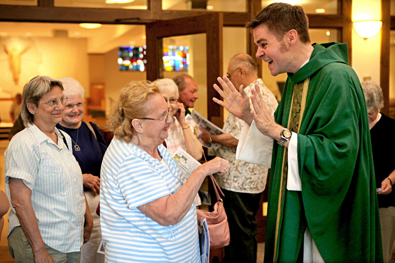 The Rev. Christopher Klusman signs with Lila Dye as he greets parishioners after celebrating Mass in American Sign Language last month at St. Roman Catholic Church in Milwaukee, Wis.