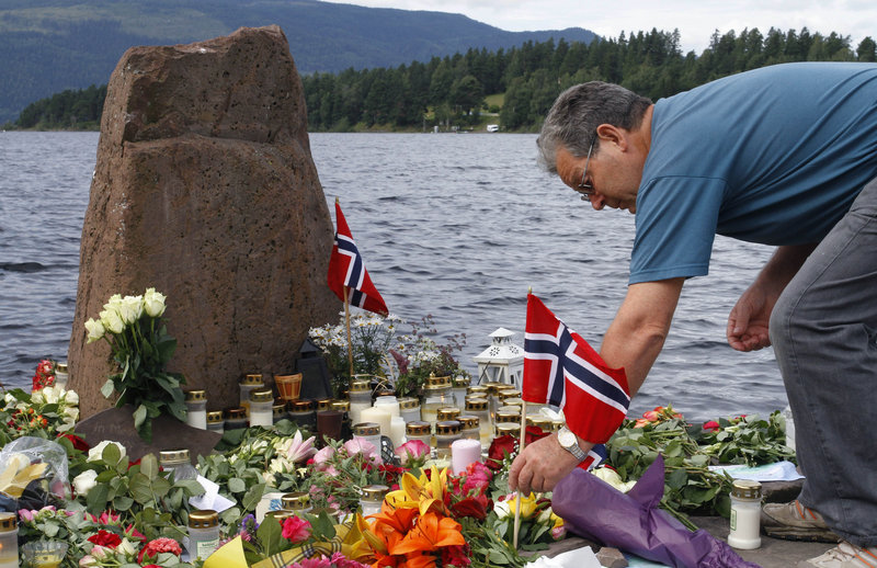 A mourner places a Norwegian flag among flowers on Utoya island, where Anders Behring Breivik killed 69 people last month.