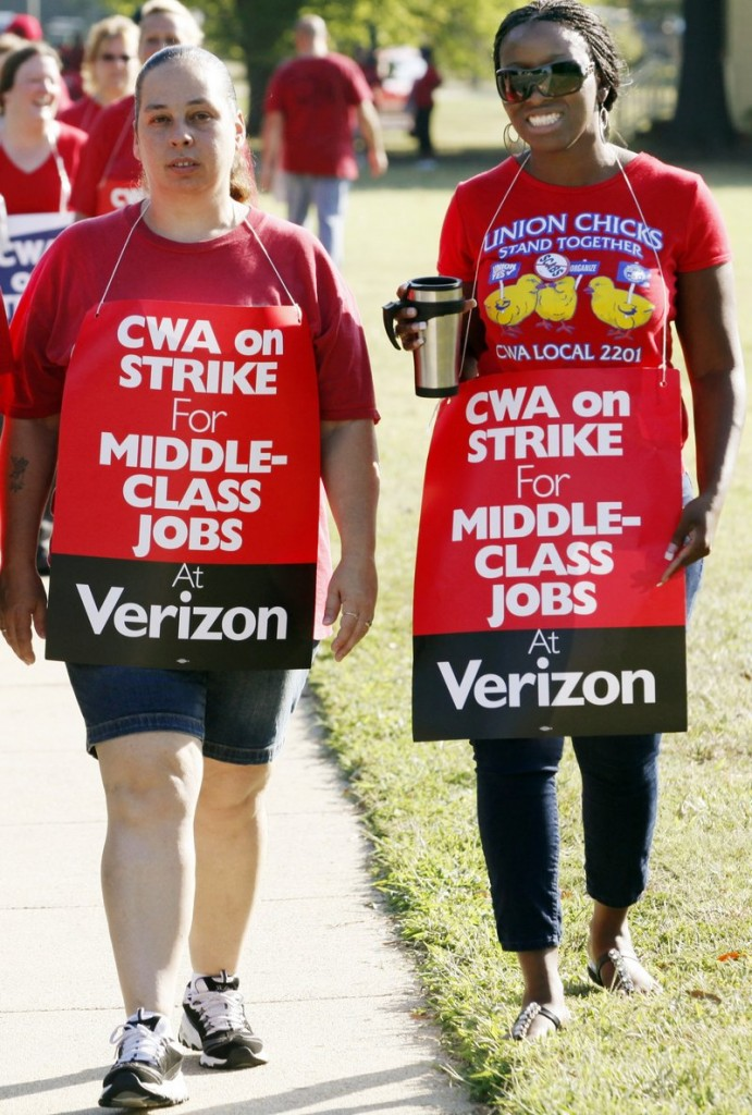 Verizon strikers Crissy Carneal and Nikki Robinson walk the picket line Aug. 8 in Henrico County, Va. The strike involved employees in nine states.