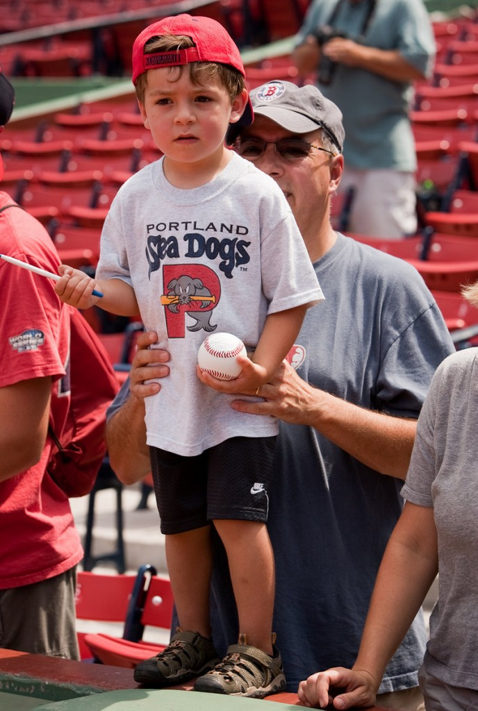 Drew Pulsifer, 4, of Andover, Mass., is held up on the wall by his father, Rich, while seeking autographs before the Sea Dogs' game at Fenway Park.