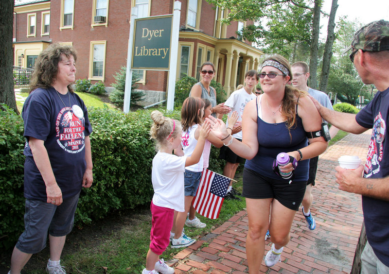 Kathy McDonald of Casco, far left, and her husband, John Williams, far right, and family greet participants in the fourth Run for the Fallen Maine on Sunday in Saco. Their son Sgt. Edmund W. McDonald was killed in Kabul, Afghanistan, in 2007.