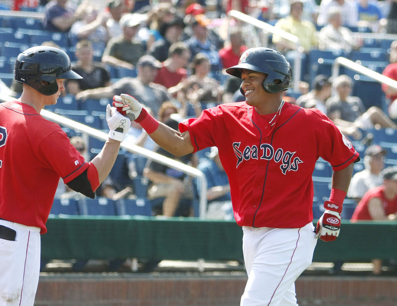 Jeremy Hazelbaker, left, greets Reynaldo Rodriguez at the plate after Rodriguez hit a home run in the bottom of the fourth inning Sunday. Five home runs were recorded Sunday, three by the Sea Dogs, in a 7-6 loss, which capped a three-game series sweep by the Mets.